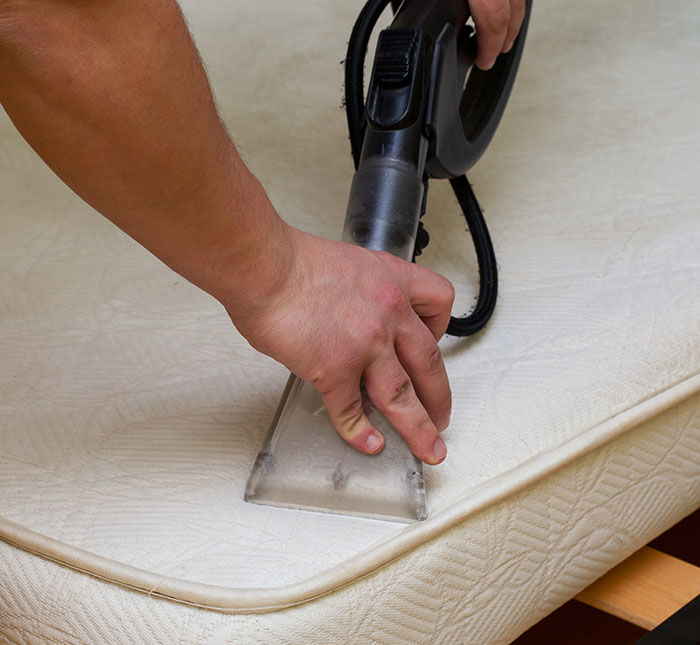 man cleaning mattress with machine