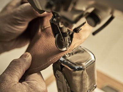 man stitching leather